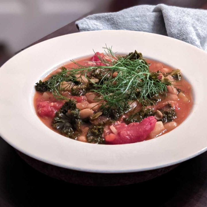 Photo of a bowl of tuscan bean soup on a wooden table, with a cloth napkin
