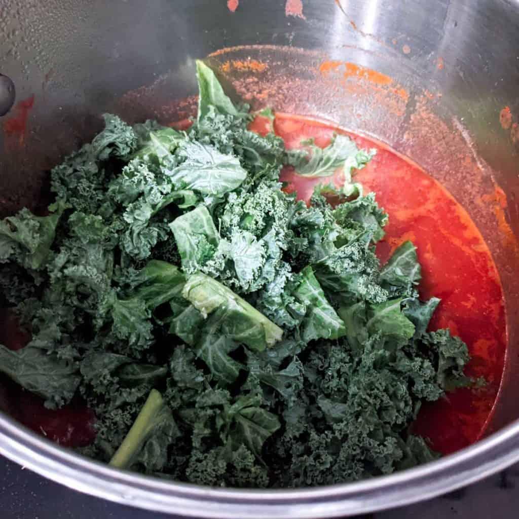 photo of adding fresh kale to tuscan soup