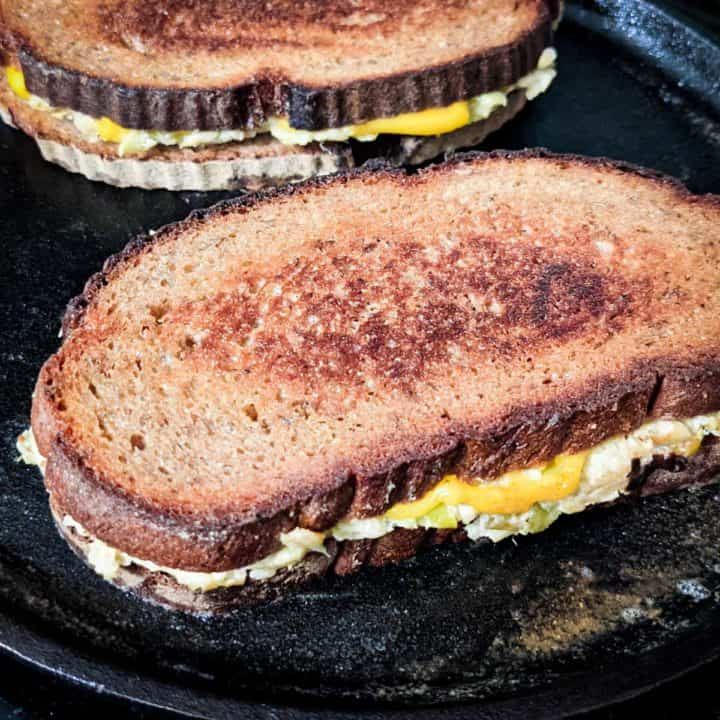 Photo of a cast iron pan with two vegan broccoli grilled cheese sandwiches